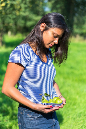 horticultural: European woman holding green pears in shirt outdoors in orchard Stock Photo