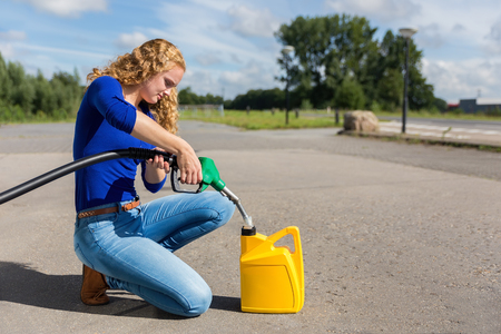 Dutch woman filling yellow can with gasoline hose outdoors