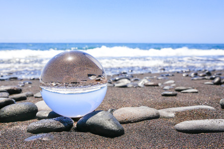 Crystal ball on stonyt beach in Madeira Portugal Stok Fotoğraf - 66339680