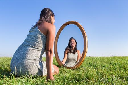 Mujer de rodillas en la hierba mirando su imagen reflejada en el Foto de archivo - 67195085