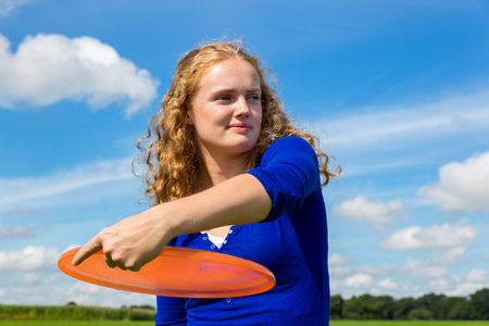 Young caucasian woman holding orange disc outdoors against blue sky Stock Photo