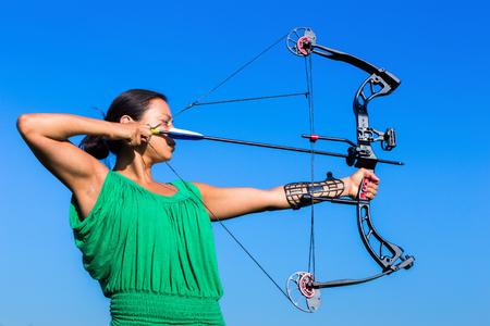 poleas: Joven de pelo negro mujer con el objetivo de flecha de arco compuesto en el cielo azul