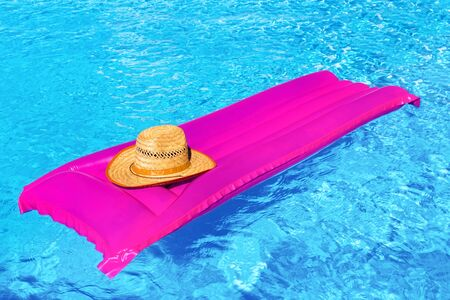 Pink air bed with straw hat in blue swimming pool
