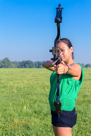 poleas: mujer holandesa que apunta con el arco y la flecha en la naturaleza