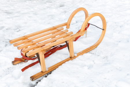 Wooden children sleigh in winter snow