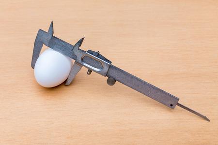 clamped: Vernier caliper measuring white chicken egg on wood Stock Photo