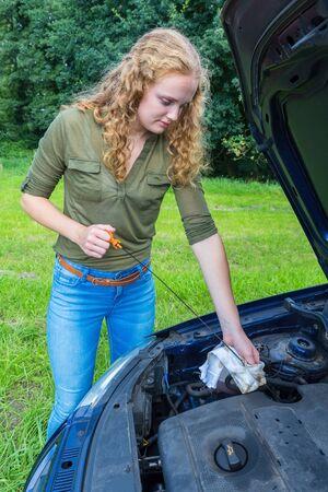 Dutch woman investigates car oil level with dipstick