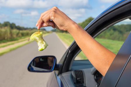 irrespeto: Brazo femenino arrojar desechos de fruta fuera de la ventana de coche