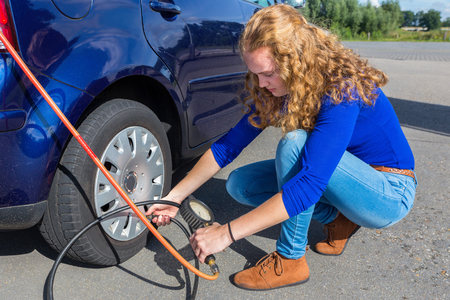 air pressure: Female driver checking air pressure of car tire outdoors