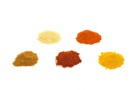 Heaps of five seasoning spices isolated on white background