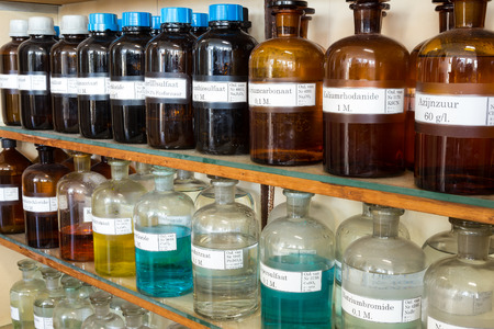 Rows of chemicals in glass bottles on shelves at chemistry on secondary school