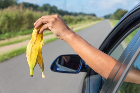 Female arm throwing  fruit waste out of car window