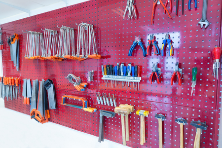 Many tools hanging at pegboard in classroom of school Stockfoto