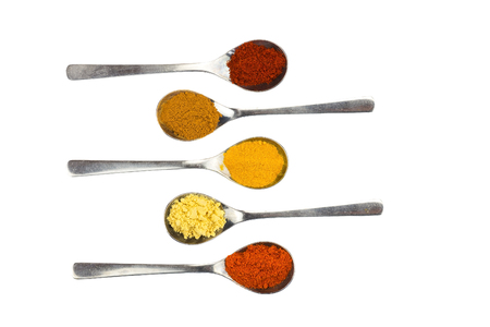 Various seasoning spices on metal spoons isolated on white background Stock Photo
