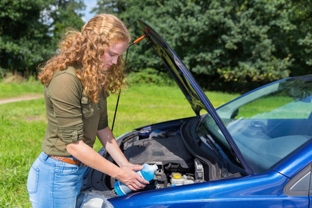 Young caucasian woman filling car reservoir with windshield wiper fluid