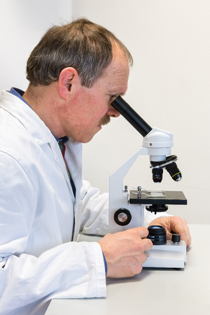 Physician in lab coat researching with microscope
