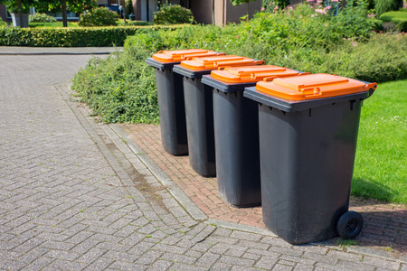Row of european grey waste bins along street