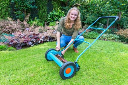 grass cutting: European teenage girl fixing lawn mower on green grass
