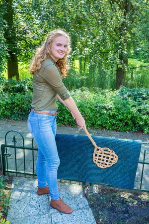 Caucasian teenage girl beating door mat with carpet beater Stock Photo