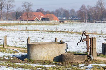 Dutch water pump and well in winter snow landscape Zdjęcie Seryjne - 73188097