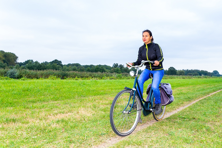 young colombian woman rides bike  on path in european nature