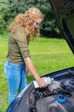 refilling: Young caucasian woman filling car cooling system with coolant in white bottle outside