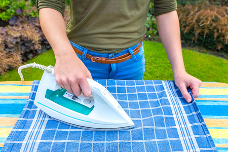 Young woman ironing tea towel with iron outdoors Stock Photo