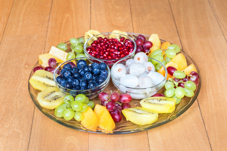 Glass scale with various fresh summer fruits on wooden floor