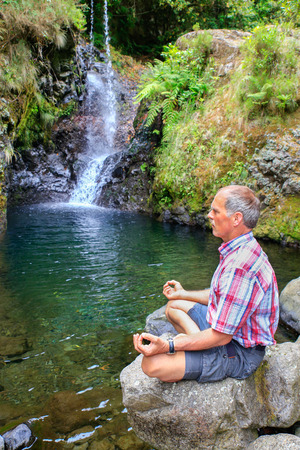 transcend: Dutch man sitting on rock meditating near waterfall in Portugal