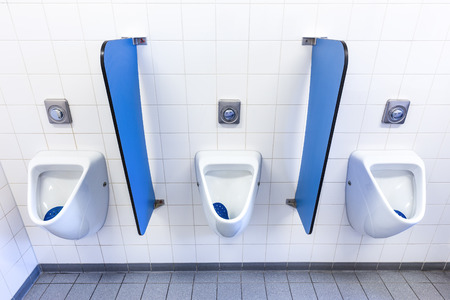 sink drain: Urinals for boys on white wall with blue partitions in high school