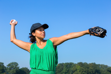 Woman with baseball glove and cap throwing baseball outdoors Stock Photo