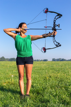 Young colombian woman shooting arrow of compound bow in meadow