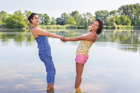 Two female friends standing together in natural water