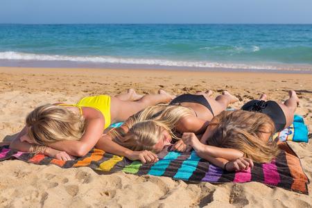 Trois filles blondes bronzer ensemble sur la plage avec la mer