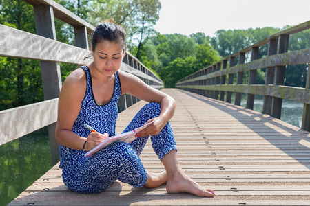 Young female writer sitting on wooden bridge in nature
