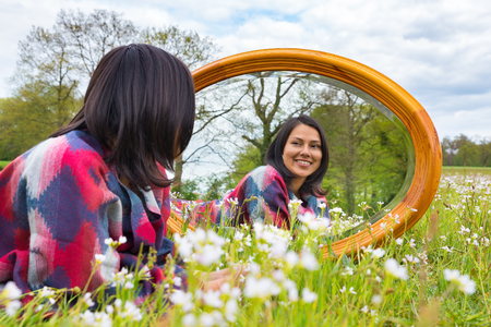 Young colombian woman lying with mirror in blooming meadow Stock Photo