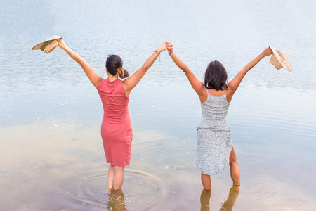 Two happy friends standing together in water of lake