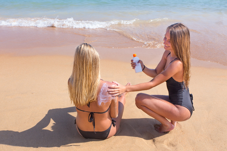 Young dutch woman rubs sunscreen on skin of girlfriend