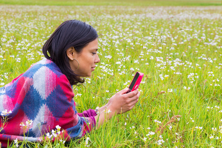 Lying Colombian woman phoning with mobile phone in meadow Stock Photo