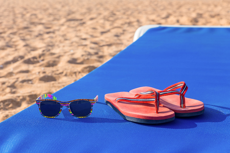 Bath slippers and sunglasses on blue sunbed at beach
