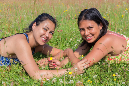 Two women lying opposite of each other in green pasture