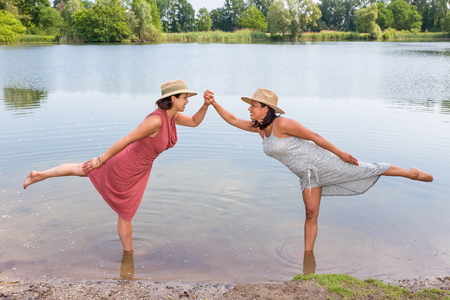 Two friends stand together on one leg in water of lake Stock Photo