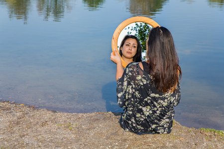 Young woman looking at mirror image near water Imagens