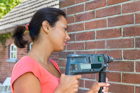 Young colombian woman holding drilling machine on brick wall