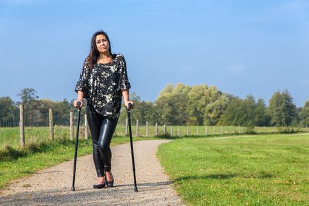 Disabled young woman walking on crutches in park Stock Photo