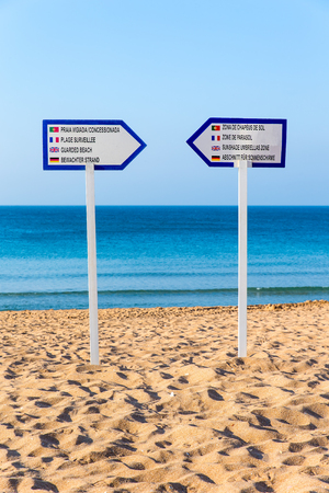 Two information signs stand on sandy beach at sea
