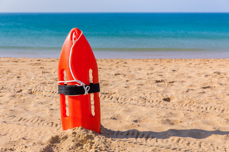 Orange buoy standing on sandy beach with blue sea Stock Photo