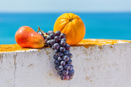 Grapes orange and pear lying on wall with sea and sky