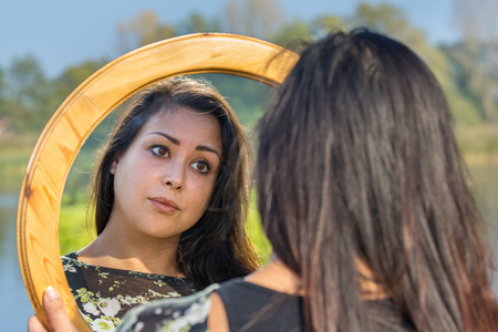 Young woman looking at mirror image in nature