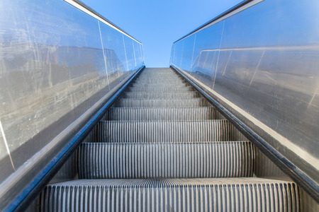 Metal empty escalator outside with blue sky